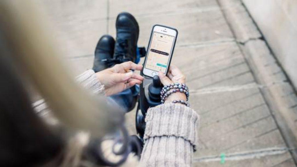 Una mujer usuaria de silla de ruedas, de la que solo se aprecia parte de su cabello largo, los brazos con un suéter gris, y los pies con botas negras sobre el descansapies de la silla de ruedas. La mujer sostiene en sus manos un teléfono celular en el que se aprecia una aplicación de transporte.