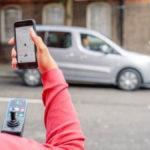 Fotografía que muestra parte de una persona usuaria de silla de ruedas que sostiene, que está de espalda, que en la mano derecha sostiene un teléfono celular donde se ve abierta una aplicación digital de transporte. La persona está en la calle y frente a ella se ve un vehículo color gris plata.