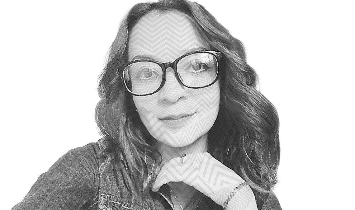 Fotografía a blanco y negro, formada por líneas del rostro de Alma Fernández, una mujer joven de rostro ovalado y ojos grandes que utiliza anteojos; aparece con cabello ondulado, suelto y tiene el rostro ligeramente recargado en su mano izquierda, lleva puesto un anillo en su dedo índice y una pulsera de cadena en la muñeca, trae puesta una chamarra de mezclilla, sonríe levemente frente a la cámara de forma.