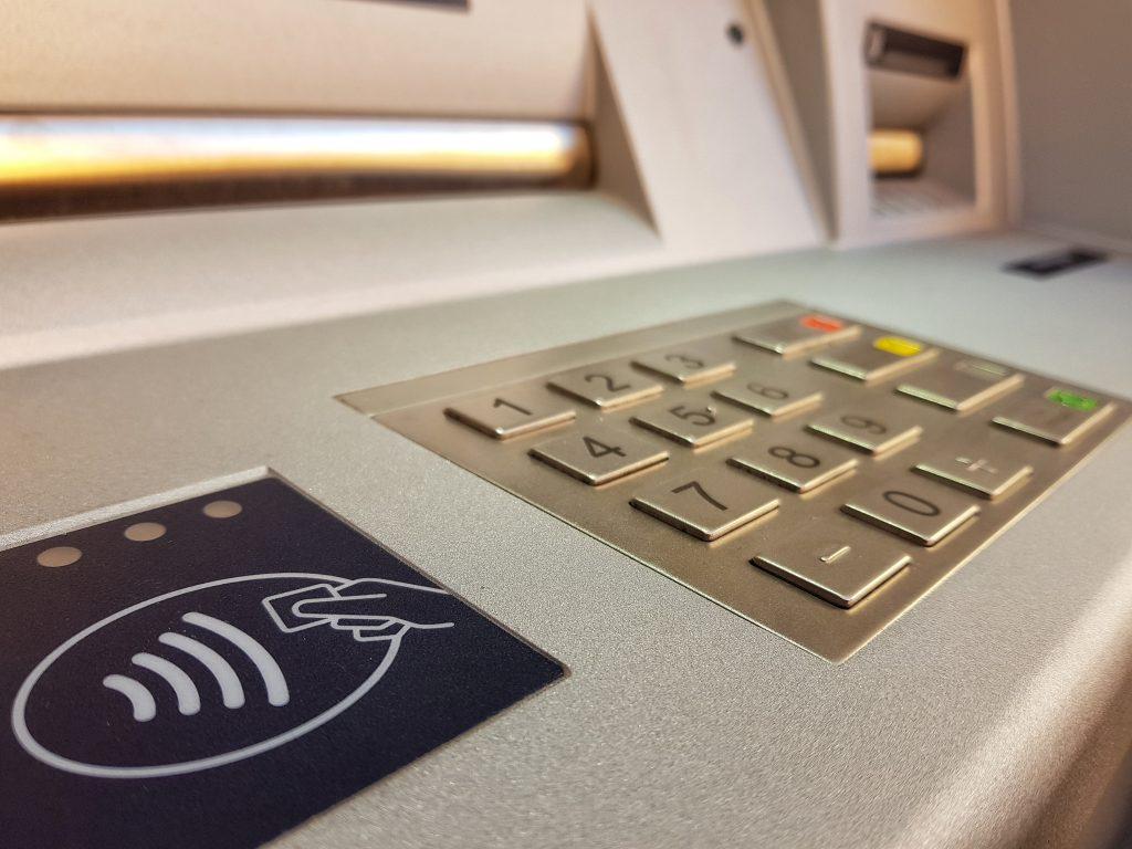 Fotografía del teclado de un cajero automático color plateado, en primer plano se alcanza a apreciar los botones del cero al nueve con puntos que indican la numeración en el sistema braille, y un sensor para tarjetas de color negro.