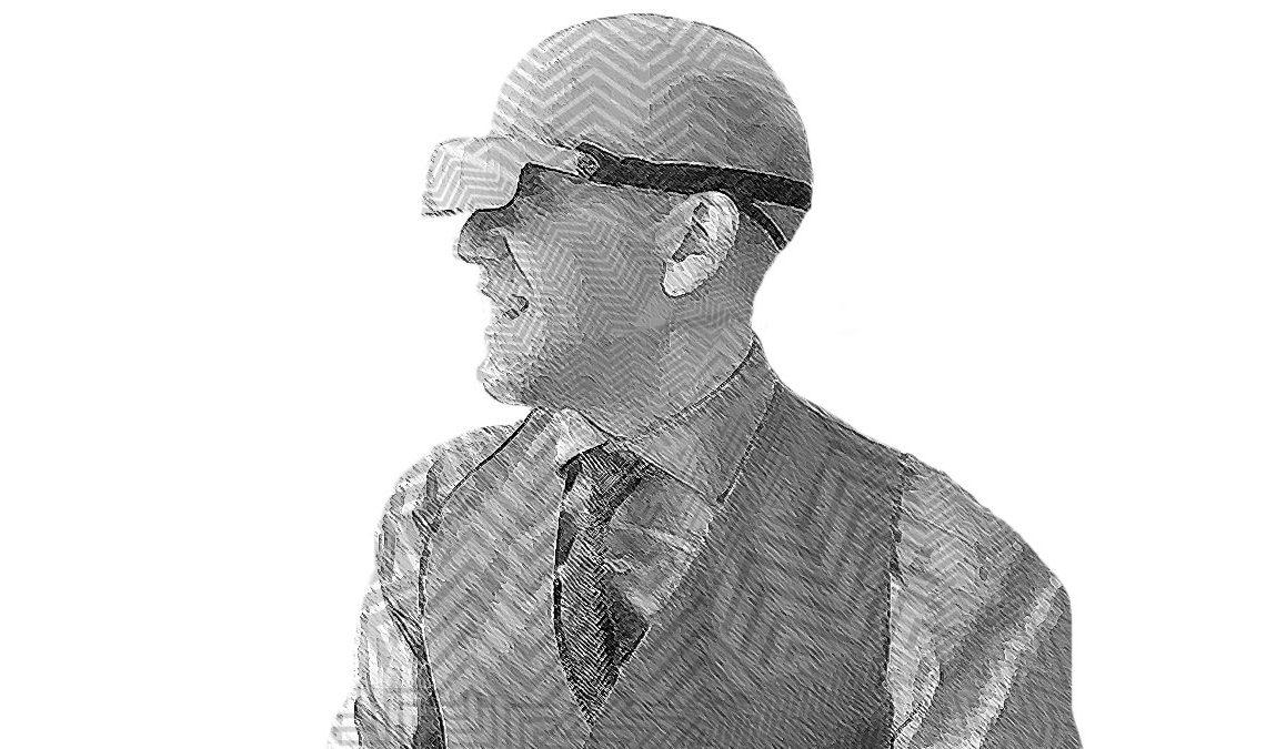 Fotografía en blanco y negro con efecto de líneas sobre el rostro de Daniel Ríos Villa, un hombre joven, calvo, aparece mirando al lado izquierdo, sonriente, trae puestas unas gafas anchas, especiales para personas con discapacidad visual, con barba de candado poco tupida, trae puesto un chaleco traje formal con corbata y camisa.