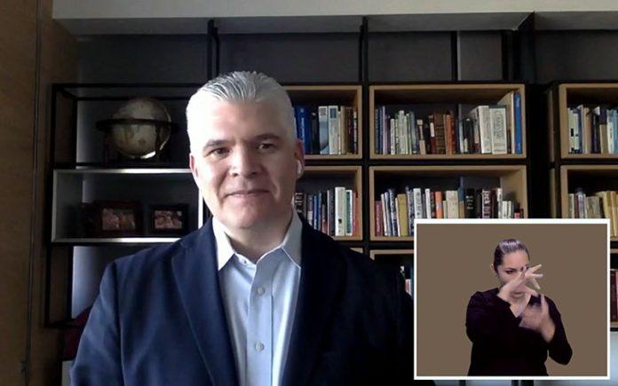 Captura de pantalla de videoconferencia en donde aparece Josune González, Gerente de Diversidad e Inclusión en AT&T México, un hombre de cabello cano, tez blanca, que aparece frente a la cámara vestido de saco negro y camisa azul con un airpod color blanco en el oído izquierdo; en un recuadro izquierdo en la esquina aparece una mujer adulta, interprete de señas, tiene cabello color café recogido en una coleta, una blusa color negra y tiene las manos frente a su rostro.