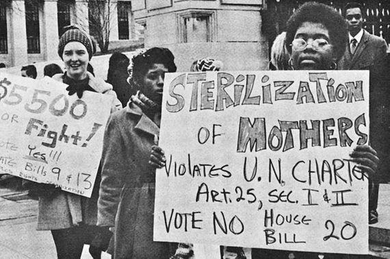 """Fotografía a blanco y negro de protesta con imágenes difuminadas, al frente una mujer afroamericana de cabello crespo, con anteojos sobre su rostro, sostiene un letrero que dice: """"sterilization of mothers violates U.N. Charter Art. 25, Secc. I y II. Vote NO House Bill"""" cuya traducción es """"La esterilización de las madres viola la Carta de las Naciones Unidas, Artículo 25, Secc. I y II. Vota NO al proyecto de ley de la Cámara""""."""