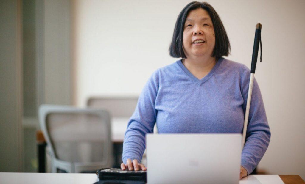 Fotografía de Microsoft que muestra a una mujer de mediana edad, sentada frente a su computadora. Ella está de frente y sonríe. Tiene cabello negro, lacio, peinado de raya en medio y le llega al mentón. Usa una blusa en cuello en v y manga larga. Con su mano izquierda opera un lector de pantalla, y con el brazo derecho abraza un bastón que indica que tiene discapacidad visual.