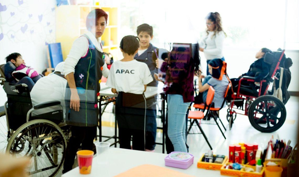 Fotografía de uno de los salones de clases de APAC, donde se ven algunas de las terapeutas y maestras con un grupo de niños y niñas con parálisis cerebral. La fotografía es a distancia y no se ven los detalles de cada persona, aunque sí se aprecia a uno de los niños que está de espaldas, al centro, y viste una playera blanca que dice APAC. Algunos de los niños están en sus sillas de ruedas y el único que ve a la cámara sonríe abiertamente.