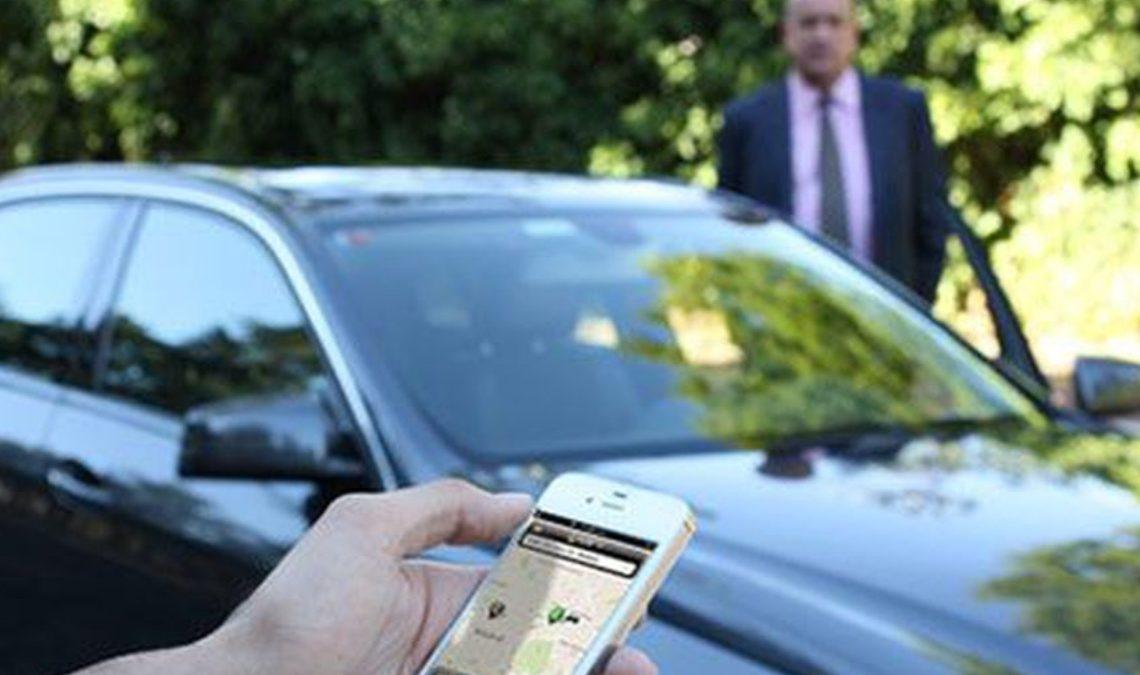 Fotografía en la que se ve un automóvil color oscuro y en un primer plano parte de una mano que sostiene un celular, y en la pantalla de este se aprecia la imagen de una app de servicio de taxis. En un plano más lejano, detrás del auto, se ve un hombre de pie que viste traje oscuro, camisa blanca y corbata.