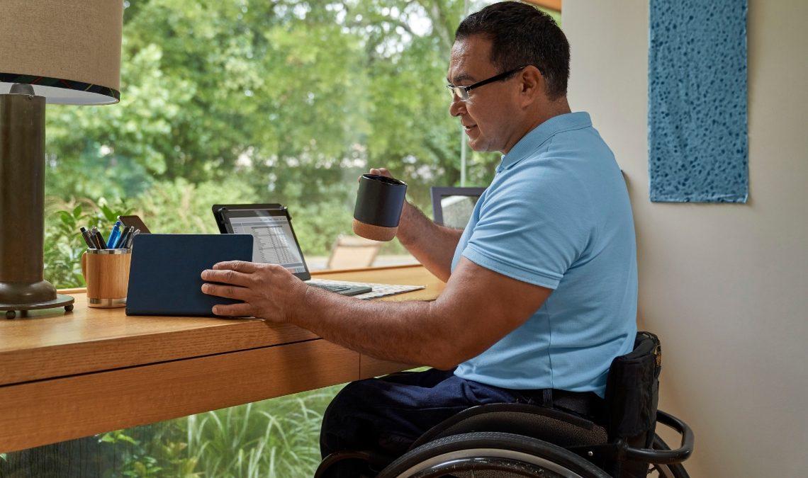 Fotografía de un hombre usuario de silla de ruedas. Está sentado, de perfil. Es de edad mediana, tiene el cabello muy corto y oscuro. Usa lentes y viste camiseta azul claro y pantalones azules. Está ubicado frente a una mesa/escritorio, colocada ante un gran ventanal donde se ve un jardín y árboles. El hombre está frente a la pantalla de una laptop y con la mano izquierda sostiene una tablet. En la mano derecha tiene una taza y la levanta.