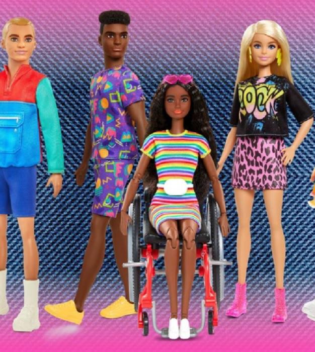 """Fotografía de cuatro de los modelos de la colección Barbie Fashionistas. La muñeca rubia está de pie a un costado, con su brazo izquierdo doblado y posa su mano en la cadera, lleva puesta una falda con estampado animal print y una playera de color negro con la palabra """"Rock"""" en ella; en el centro, en una silla de ruedas moderna, en color negro, rojo y plateado, una modelo de piel oscura, con cabello muy largo, color café y rizado, sostiene con unos lentes rosa en su cabeza, como si fueran una diadema y lleva un vestido de colores a rayas horizontales. A su derecha están dos modelos varones, uno de piel oscura con un conjunto de playera y short color lila y una par de figuras geométricas de colores pastel y otro muñeco de cabello rubio y tes blanca, lleva puesta una sudadera rojo con azul y un short color azul. Los cuatro modelos llevan atuendos de moda en colores fosforescentes y alegres. (Foto: Barbie Mattel)."""
