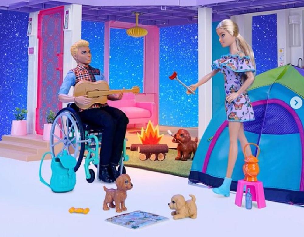 Imagen en donde se aprecian dos de los principales personajes de la colección Fashionistas. La muñeca Barbie, rubia y con cola de cabello, lleva un vestido de hombro caído, color azul, estampado, corto y con botines azules. Mientras Ken, a la izquierda, es un usuario de silla de ruedas. Viste pantalón oscuro, botines negros, y una camisa que combina un estampado a cuadros, en color rojo, amarillo y blanco, con las mangas azul claro. Ken sostiene en sus manos una guitarra. En la imagen también aparecen tres perritos de diferentes tonalidades de color café, uno de ellos se encuentra junto a una fogata. Y hay una tienda de campaña atrás de Barbie. Hay también una mochila al lado de la silla de ruedas de Ken y un banquito color rosa con una linterna de gas color naranja a lado de la pierna derecha de Barbie. (Fotografía: Barbie Mattel).