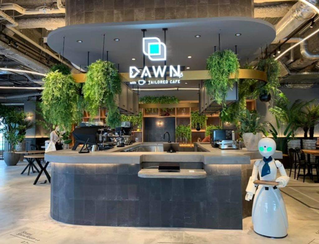 Acceso al Dawn Café en Tokio, donde se ve la barra de recepción en tonos de gris, algunas pantallas sobre ella, y al lado uno de los robots humanoides esperando. La decoración del lugar destaca por las plantas, desde enormes hojas elegantes en macetones de fondo hasta helechos de gran tamaño que cuelgan desde el techo.