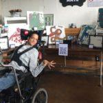 Fotografía de un joven con discapacidad en una silla de ruedas adaptada para integrar su equipo tecnológico de comunicación aumentativa y adaptativa. Él está semi inclinado sobre su espalda y tiene su brazo izquierdo doblado y con la mano saluda, mientras visita una exposición de arte realizada por personas con discapacidad. Las obras de arte, de diferentes tamaños, están colocadas en mesas que forman una herradura, de tal manera que puedan apreciarse los cuadros en diferentes formatos y técnicas.