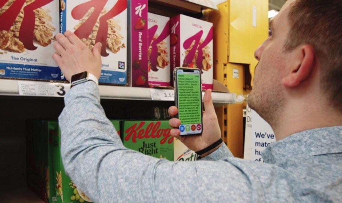 Fotografía de un hombre joven, al que solo se le ve el perfil izquierdo, en el supermercado. Está frente al anaquel de cerereales y con la mano izquierda toma una caja, mientras con la derecha sostiene un celular en el tiene una app que permite leer la información contenida en el empaque. Se trata de una tecnología diseñada para personas con discapacidad visual.