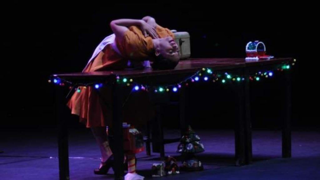 Fotografía de Erika Bernal, actriz de Teatro Ciego Mx, en escena de una obra relacionada con la Navidad, por los adornos que se ven en el escenario. Ella está inclinada sobre su espalda hasta una mesa, adornada con luces navideñas de colores y al extremo derecho de ella se ve un buzón del Polo Norte. Abajo de la mesa, está un pequeño árbol de navidad adornado y otro adorno que es semejante a una casa navideña.  Erika usa un vestido anaranjado, con holán o volante bajo y sobre el vestido un delantal blanco.    La cabeza de Erika prácticamente toca la mesa y cruza sus brazos sobre el pecho. La iluminación de la escena es muy oscura, así que solo se aprecia el vistoso vestido de la actriz y las luces navideñas multicolores.