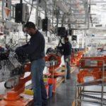 Fotografía del área de armado de motores de una planta armadora de Ford, en la que se aprecia un poco de las líneas de producción. En la fotografía se ve a dos operarios trabajando. Los dos visten ropa en color azul.