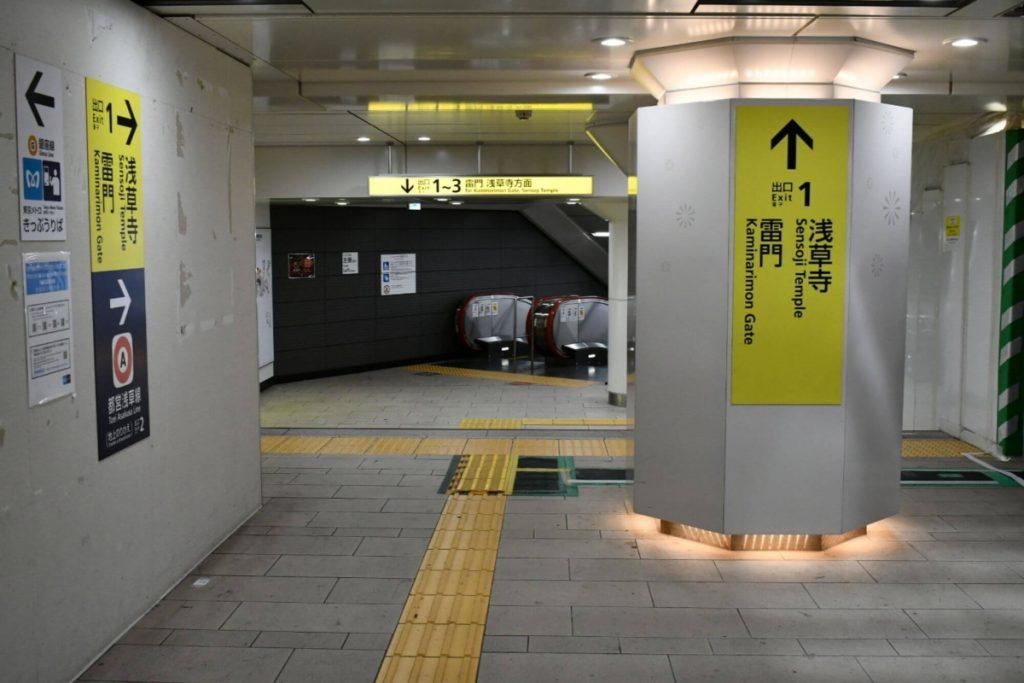 Fotografía de parte de una estación de transporte público, de la Japan National Tourism Organization, en donde se aprecia la señalización a los costados, y las filas de piso podotáctil en color amarillo, que guía a las personas con discapacidad visual hacia las escaleras y elevadores.