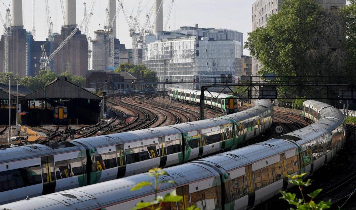 Fotografía de dos trenes de cercanías en Londres. Los vagones no se aprecian en detalle, pero fueron captados en una curva, lo que permite abrir la toma y ver en la parte trasera imágenes de una zona industrial.