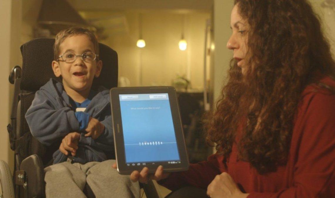 Fotografía de Microsoft que en el lado derecho muestra a una mujer de perfil, con el cabello rizado y largo, que cae sobre el suéter color vino que viste. Ella sostiene una pantalla y, de lado izquierdo, de frente y sonriente, está un niño pequeño, sentado en una silla de ruedas. Tiene discapacidad motriz y visual.