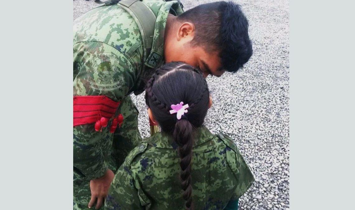 Fotografía de la secretaría de la Defensa Nacional que muestra a un papá militar con su hija. El papá está inclinado y recibe un beso en la mejilla de su hija, una menor de unos 5 años que está de espaldas, y se le peinada con dos trenzas que se hace una, y sobre ella una flor en rosa y blanco. Tanto la niña como el papá visten un traje militar, en diversos tonos de verde y con estampado de camuflaje. El hombre tiene cabello muy corto y sobre el brazo derecho porta un distintivo rojo.