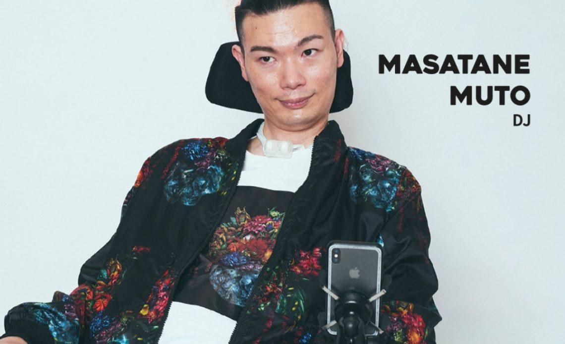 Fotografía de Masatane Muto sentado en su silla de ruedas adaptada con un soporte para el cuello y otro donde está un dispositivo que incluye un celular y que usa para comunicarse. Masatane es un hombre joven, de rasgos asiáticos y con cabello muy corto color oscuro. Como la imagen corresponde a un festival de moda, usa uno de los atuendos que diseña dentro de lo que es llamando moda adaptativa para personas con discapacidad. Es una especie de saco amplio, color negro, con un estampado en flores, que se replica en la parte frontal de una camisa que combina el blanco con la parte oscura a juego con el saco.