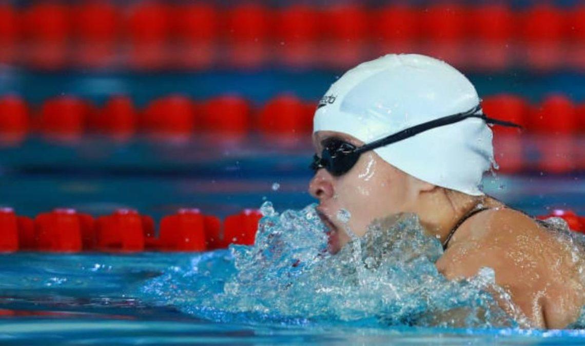 Fotografía de Naomi Somellera, la campeona paralímpica mexicana de natación. En la imagen, se le ve de perfil, nadando en una alberca con carriles rojos. Naomí lleva gorro de natación blanco y sobre él sus goggles negros. La fotografía fue captada justo en el momento en el que jala aire y en torno a ella se ve el agua de la alberca agitada, como en una pequeña ola.