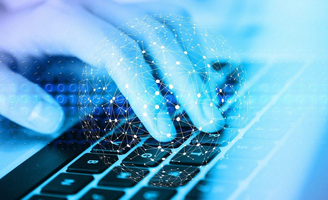 Composición gráfica que muestra los cuatro dedos de una mano sobre un teclado de computadora; la imagen de la mano queda un tanto desvanecida. Sobre ella y el teclado se colocó un gráfico de puntos luminosos que crean una especie de círculo y que reflejan casi de manera inadvertida códigos informáticos.