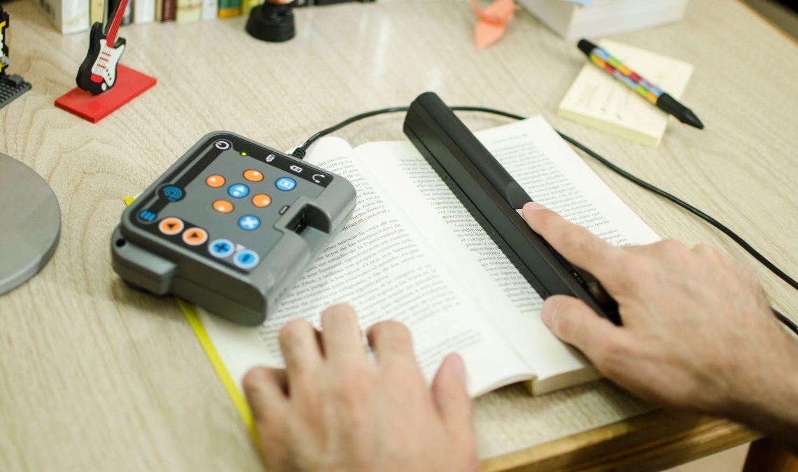 Fotografía de dos manos. La izquierda se apoya en un libro abierto. La derecha toma un scanner que le permite transformar el texto a voz. El lector scanner está conectado al dispositivo procer, que tiene forma rectangular, con botones y del tamaño de la mano.
