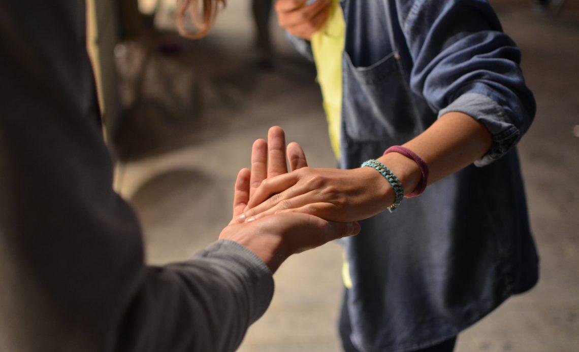 Fotografía de dos manos que se estrechan, del lado izquierdo se ve el brazo de un hombre que viste sudadera gris con la mano extendida, sobre ella, estrechándola, se ve la mano d una mujer, quiene lleva dos pulseras, una azul y otra morada, se alcanza a ver la mitad de su tronco, viste blusa amarilla y encima una camisa abierta azul.