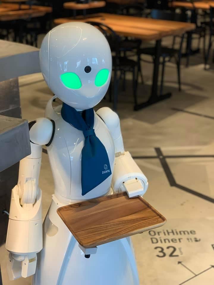Fotografía de uno de los robots que sirven como meseros en un café en Tokio. Tiene figura humanizada, en color blanco, con una pañoleta al cuello simulando una corbata. Sus brazos son articulados, lo que le permite doblarlos. Sus manos son una especie de pinza, que le permite portar una charola, que parece de madera. Su cabeza es ancha en la parte superior y más delgada en la inferior, y destacan en ella sus ojos enormes, alargados e iluminados con una luz verde.