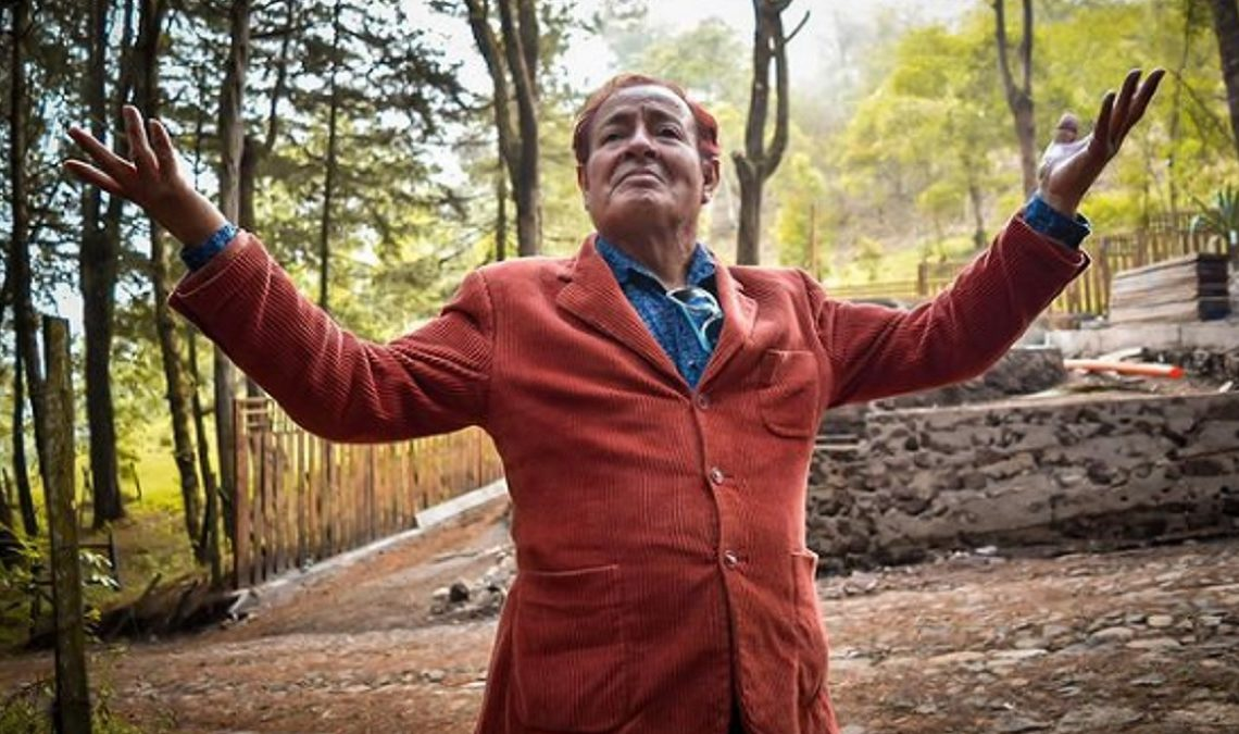 Fotografía del actor Sammy Pérez, quien murió este viernes 30 de julio. En la imagen está en un bosque, con una zona arbolada y caminos de piedra detrás de él. Está de pie, con los brazos y el rostro levantados, y sonríe un poco. Usa un saco largo, color ladrillo, cerrado con botones del mismo color, y una camisa azul que se le ve bajo el saco.