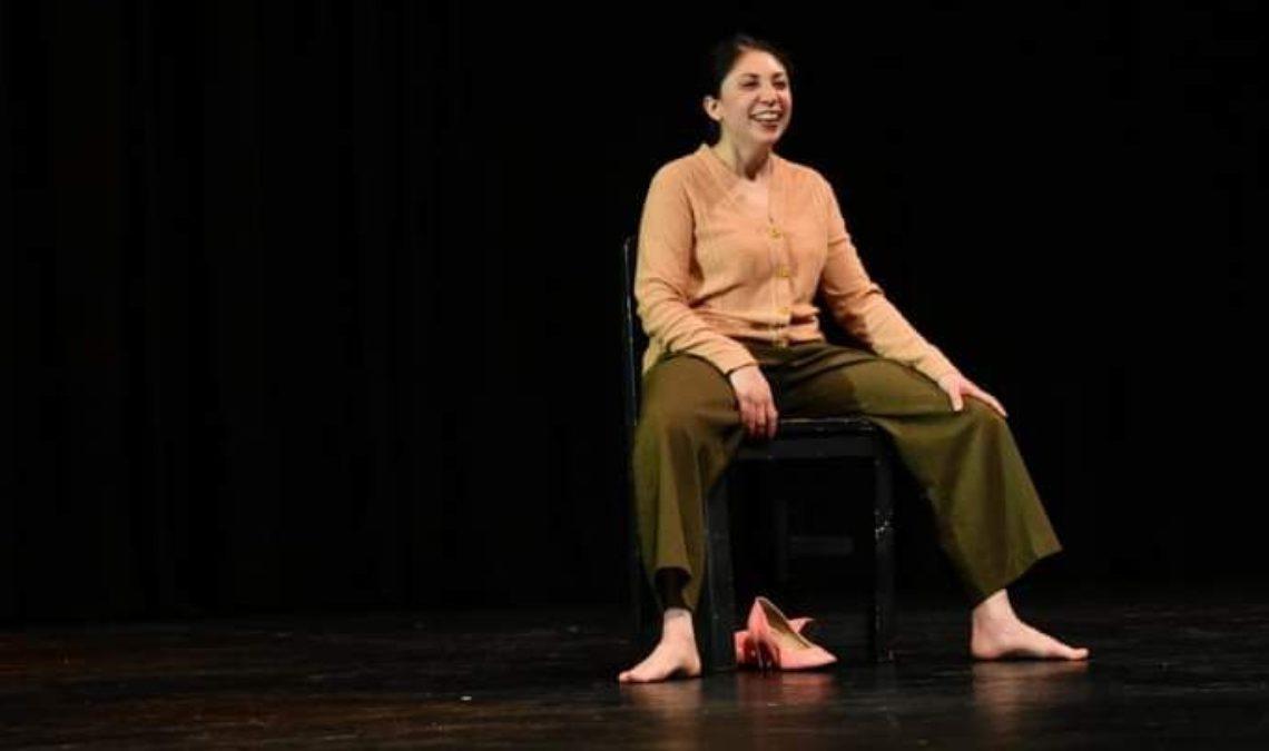 Fotografía de Erika Bernal, una joven mujer que es actriz de Teatro Ciego. Ella está sobre un escenario oscura, donde todo el foco es ella, que está sentada muy sonriente y descalza. Sus zapatos están debajo de la silla donde está. Usa cabello recogido, viste blusa color salmón y pantalón café, lo que le permite abrir las piernas ampliamente, en posición relajada y con los brazos descansando sobre las piernas.