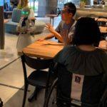 Fotografía de dos personas, una mujer de espaldas usuaria de silla de ruedas, y un hombre sentado de tres cuartos, frente a una mesa de un café en la ciudad de Tokio, que es atendido por robots humanizados operados a distancia por personas con discapacidad. Al lado del hombre se ve uno de los robots, vestido de blanco, con una corbata negra y grandes ojos que se iluminan con una luz verde. El robot lleva una charola. Otro robot está del otro lado de la mesa de las dos personas sentadas a la mesa.