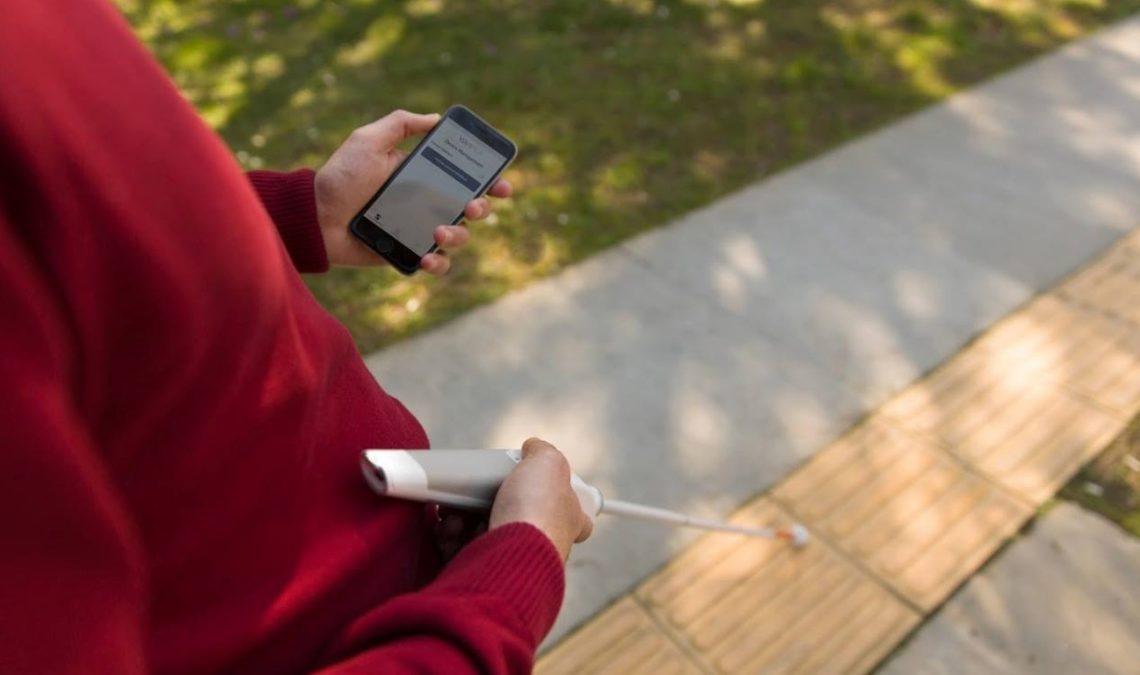 Fotografía de un hombre, del que solo se ve el suéter color vino que lleva puesto, ya que la imagen se centra en el bastón blanco que lleva en la mano derecha, mientras en la izquierda tiene un teléfono celular que le permite controlar mediante una app el bastón, al que le fue colocado un dispositivo en la parte superior.