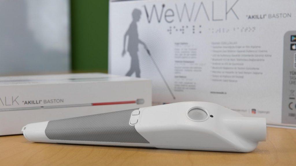 En el primer plano de la imagen se aprecia el dispositivo WeWalk que funciona con una app y puede ser instalado en cualquier bastón para personas con discapacidad visual. El dispositivo está colocado sobre una superficie de madera, es blanco con detalles en gris, y su forma es semejante a un cono. En la parte superior está un orificio para colocar el bastón y tiene un par de botones. Atrás del dispositivo, están dos cajas. Son  los empaques que lo contienen. Las cajas son blancas y en gris se aprecian el nombre WeWalk y una serie de instrucciones que son ilegibles en la fotografía. La caja también tiene la silueta de una persona con discapacidad visual usando un bastón.