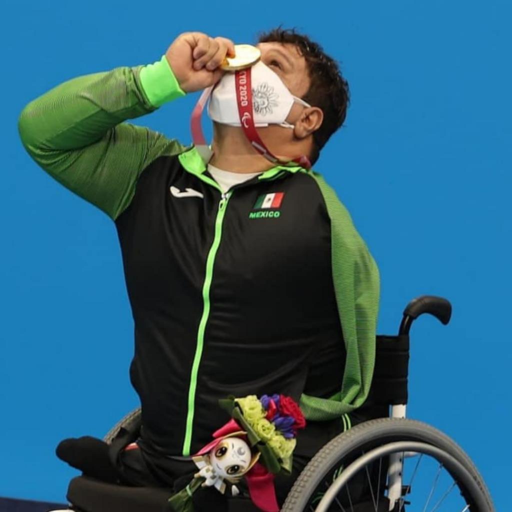 Fotografía de Arnulfo Castorena nadador paralímpico. Es usuario de silla de ruedas y en la imagen se le con un cubrebocas blanco, que solo permite verle el ojo izquierdo, ya que el derecho está cubierto por la medalla de oro que sostiene en la mano derecha y lleva hasta su frente. Usa la chamarra del equipo mexicana, negra con mangas y cierre verde, que permite ver la amputación de su brazo izquierdo.
