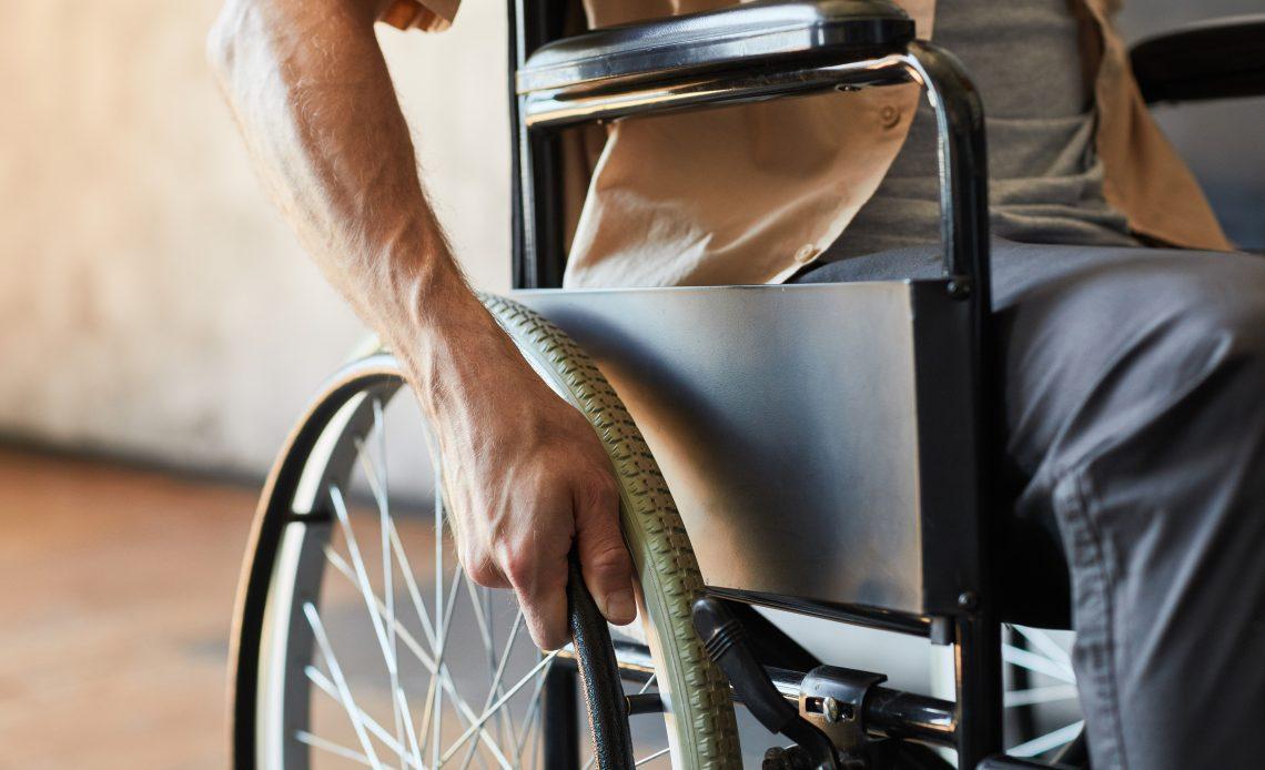 Fotografía en donde se alcanza a apreciar brazo izquierdo de una persona usuaria de silla de ruedas que toca la rueda de la silla color negra, la persona lleva puesta una camisa color beige con playera gris y pantalón negro.