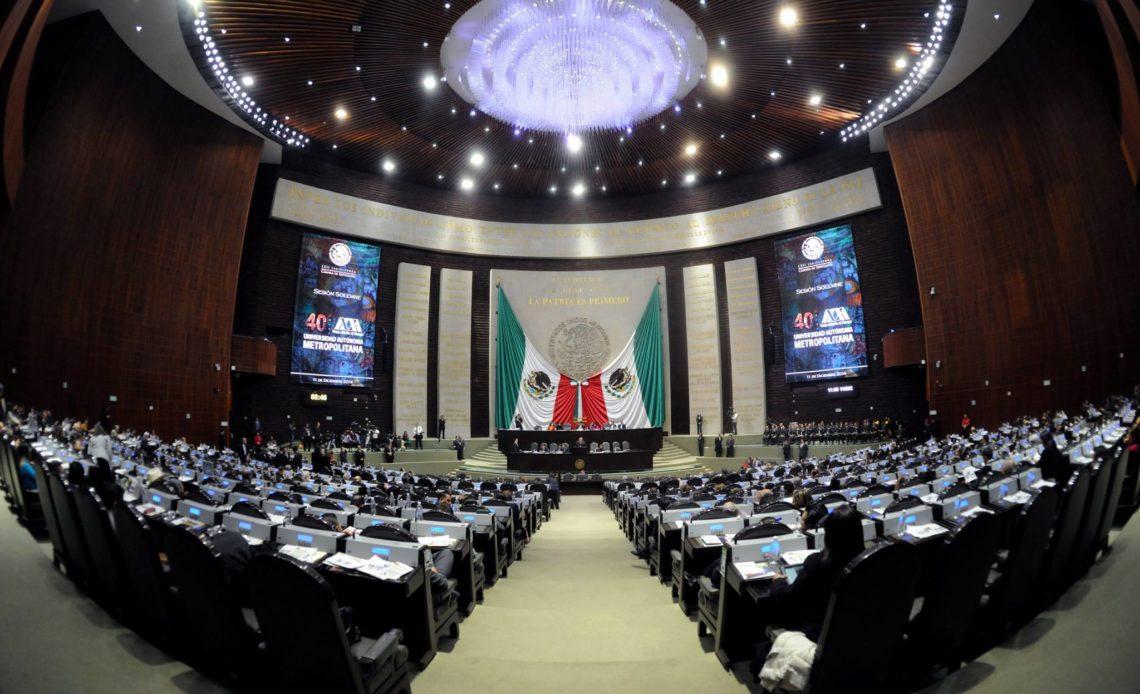 Fotografía panorámica de la Cámara de Diputados, una gran sala de conferencias dos banderas de México colocadas a lo ancho y largo de todo el escenario, una de lado izquierdo y otra de lado derecho, al centro hay un pódium de madera color caoba con lugar para 14 personas sentadas, al frente del escenario hay dos bloques de asientos en la sala, los asientos son de tela color negro, en el techo tiene un gran candelabro que enciende luz de color blanco y a los costados del escenario se alcanzan dos pantallas verticales de gran tamaño que cubren la altura del escenario que reproducen un cartel de color azul marino alusivo a los 40 años de la Universidad Autónoma de México.