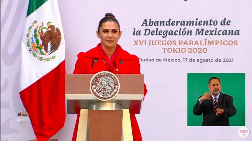 Fotografía en donde aparece Ana Gabriela Guevara, una mujer de edad adulta, cabello color negro, recogido en un chongo, tez blanca, rostro ligeramente redondo, viste un abrigo de color rojo y se encuentra detrás de un podium de madera con el símbolo de los Estados Unidos Mexicanos estampado en color dorado, detrás de ella aparece una lona que dice: Abanderamiento de la delegación mexicana XVI Juegos Paralímpicos Tokio 2020.