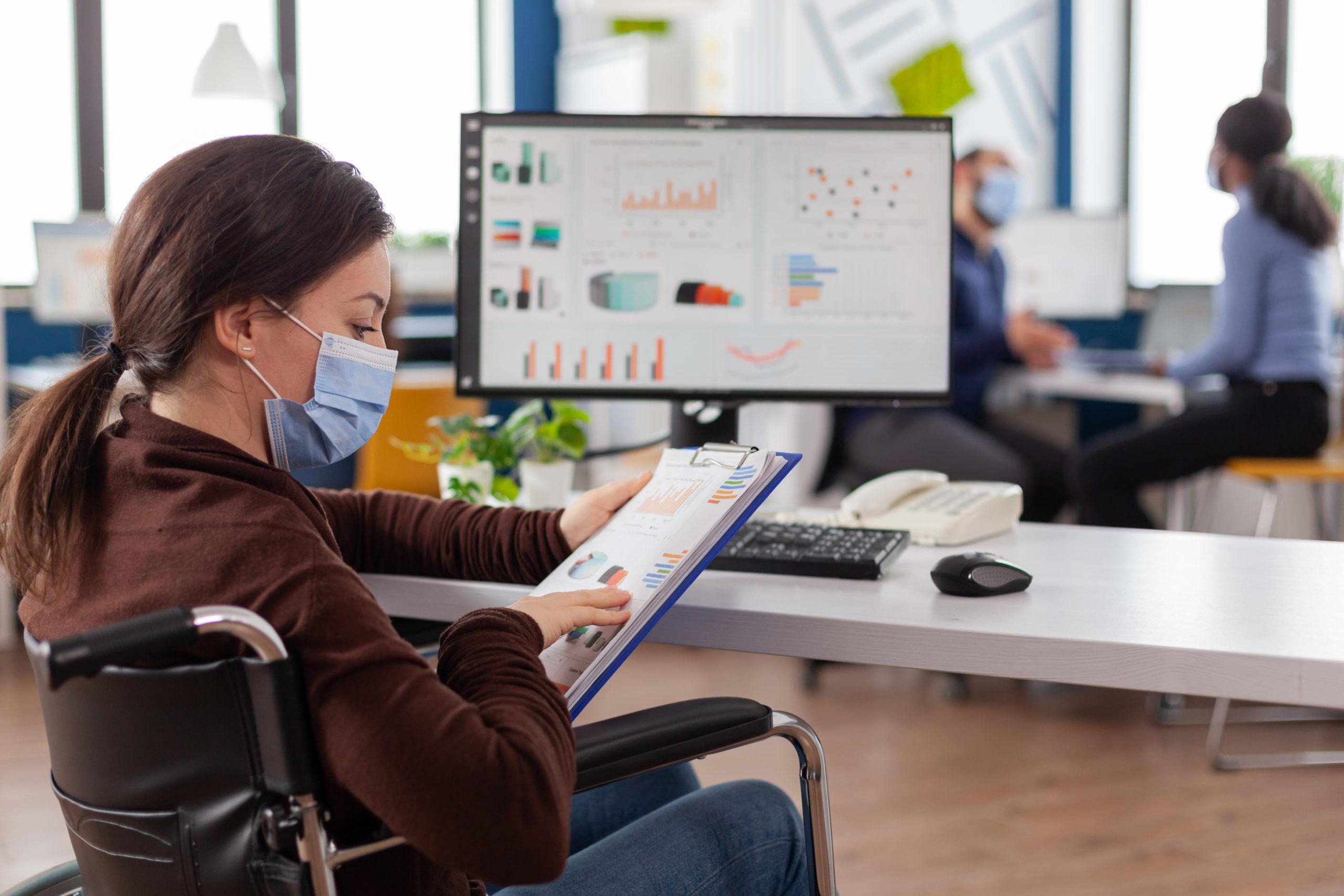 Fotografía de una mujer joven usuaria de silla de ruedas con cabello negro, largo, agarrado en una coleta, tez blanca, vestida con una blusa de manga larga de color café y pantalón de mezclilla, trae puesto un cubrebocas de color azul y en las manos tiene una papeleta color azul claro con hojas que muestran gráficas de colores azul marino y naranja, frente a ella, difumanido sobre un escritorio blanco, se encuentra una computadora de escritorio que de igual forma proyecta algunas gráficas.