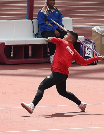 Fotografía de Eliezer Gabriel, un hombre joven de tez morena, cabello castaño oscuro, que lleva una jabalina de color morado en la mano derecha y viste una playera deportiva de color rojo y pantalón de color negro, se encuentra de pie en una pista de carreras de atletismo.