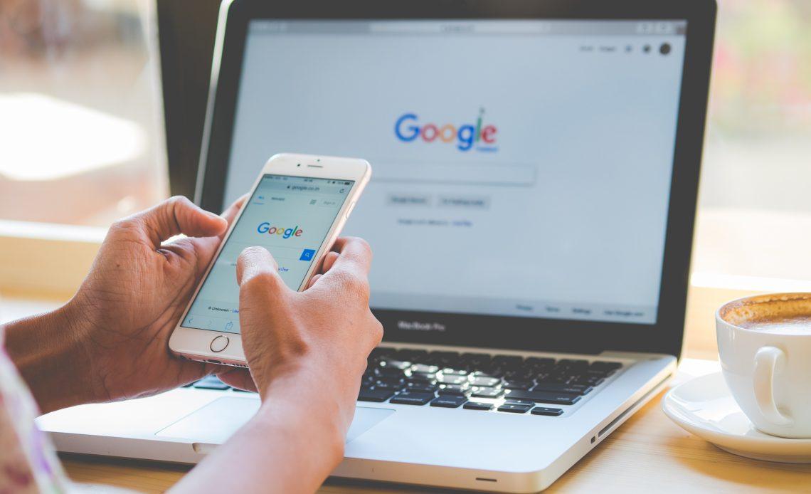 """Fotografía en la que aparece una mano sosteniendo un teléfono celular cuya pantalla refleja el buscador inicial de Google, es decir, un fondo blanco con un recuadro horizontal de bordes delgados de color negro que tiene un ícono de lupa de color blanco con fondo azul y las letras """"Google"""" en diferentes colores, la """"G"""" en azul marino, la """"o"""" en rojo, la """"o"""" en amarillo, la """"g"""" en azul marino, la """"l"""" en color verde y la """"e"""" en rojo, detràs en segundo plano aparece una laptop color gris con teclas negras en cuya pantalla de igual forma aparece el buscador de Google, a lado derecho de la computadora se encuentra una taza de café color blanca rellena de un líquido de color café claro con un poco de espuma color blanca, todo lo anterior está colocado sobre una mesa color madera clara."""