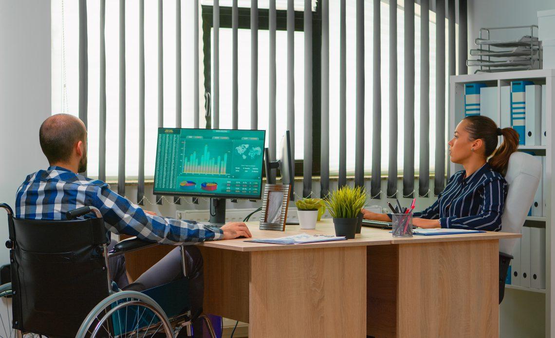 Fotografía en la que aparece un hombre de mediana edad, calvo con barba en forma de candado, vestido con camisa a cuadros de color azul con blanco y pantalón de mezclilla de color azul oscuro, es usuario de silla de ruedas, y se encuentra sentado frente a un escritorio de madera color café claro que tiene un monitor negro que proyecta gráficas de color verde esmeralda; en el otro extremo del escritorio se encuentra una mujer de cabello castaño, recogido en una coleta, vestida con blusa azul marino con franjas blancas, sentada frente a otro monitor. Al fondo se alcanza a apreciar una oficina, un estante con carpetas de color blanco y una ventana con las persianas de color gris semi abiertas.