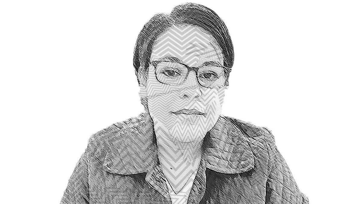 Fotografía a blanco y negro con líneas sobre el rostro de una mujer de edad joven, Itzel Hermida, que tiene cabello corto a la altura de sus orejas, rostro ovalado y ancho, sonríe ligeramente frente a la cámara y lleva puestas unas gafas de armazón ancho y chamarra con solapas en ambos lados del cuello.