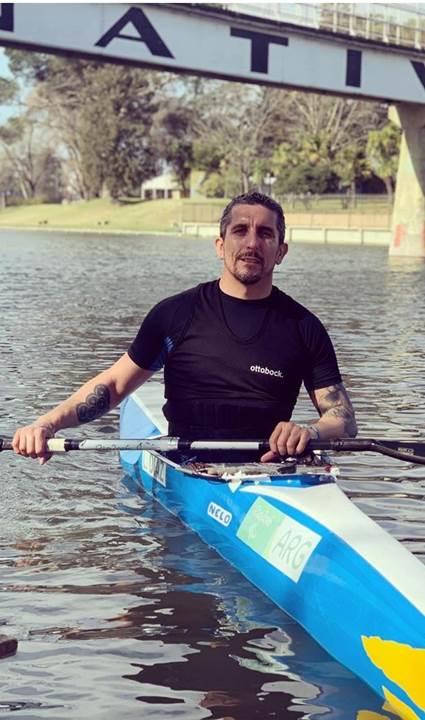 Fotografía del paradeportista de canotaje argentino Lucas Díaz Aspiroz, dentro de su kayak, que tiene los colores azul y blanco de la bandera argentina. Él viste una camiseta deportiva en color negro, tiene tatuajes en los brazos, cabello, bigote y barba de candado color negro con algunas canas, y entre sus manos toma el remo. El kayak está sobre el agua. De fondo se ve un paisaje.