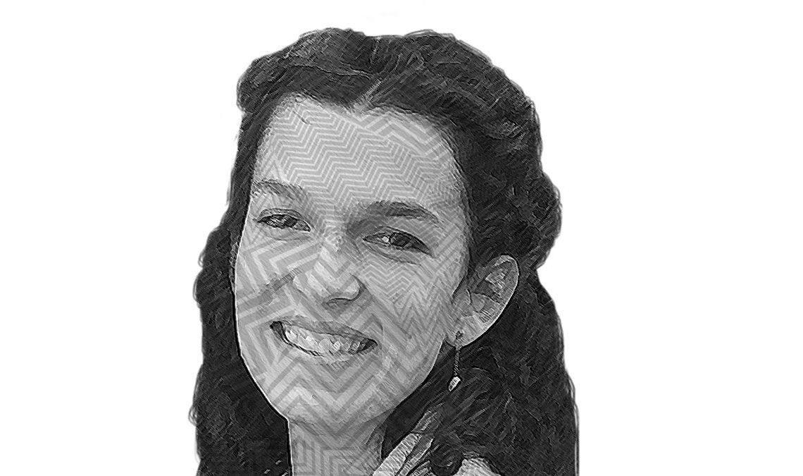 Fotografía a blanco y negro, formada por líneas del rostro de Mariel Iginiz, una mujer de edad media, con cabello rizado, recogido en media coleta, ojos pequeños ligeramente caídos, la mujer sonríe frente a la cámara.