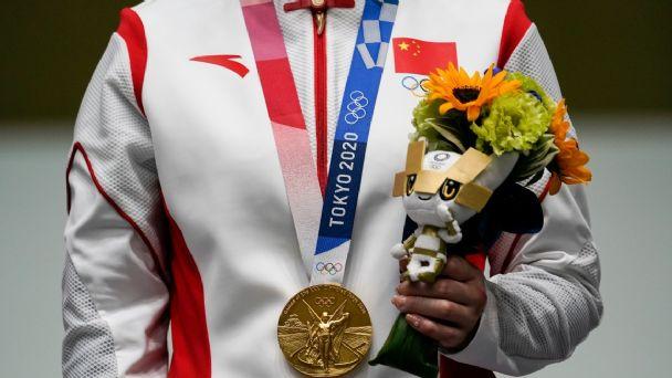 """Fotografía del pecho de una persona vestida con una chamarra blanca con franjas rojas a los costados que tiene impresa la bandera de china, la persona sostiene un ramo de flores con la mano izquierda y lleva colgada una medalla de oro del cuello, el listón de la medalla tiene impreso """"Tokio 2020""""."""
