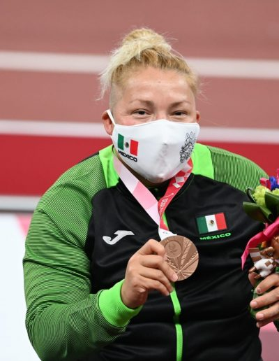 Fotografía de Rosa María Guerrero, paratleta mexicana ganadora de la presea de bronce en la categoría de lanzamiento de disco, se alcanza a preciar del dorso para arriba, lleva puesta una chamarra deportiva de color negro y mangas de color verde fosforescente, cuelga de su cuello la medalla de bronce.