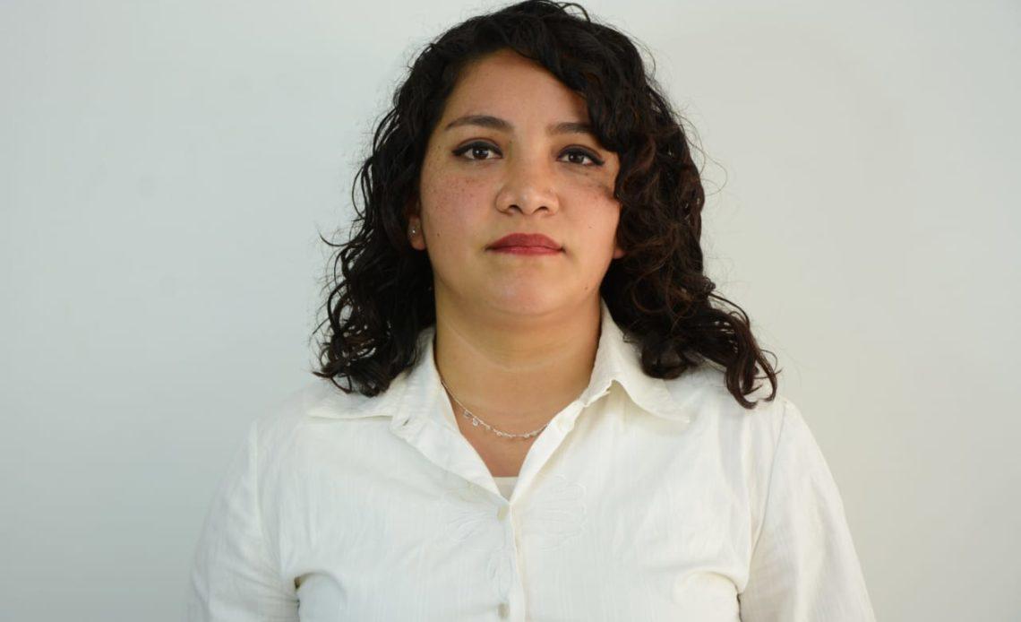 Fotografía de Norma Narváez Aguilar, una mujer joven de tez latina, cabello negro, un poco ondulado, suelto, aparece con una ligera sonrisa frente a la cámara, lleva puesta una blusa de color blanca con manga larga, el fondo de la imagen es color blanco.