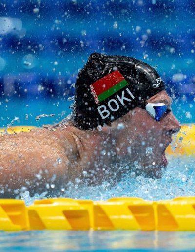 """Fotografía del rostro paratleta Boki, del equipo de Bielorrusia, saliendo de la piscina para respirar durante una competencia, en la fotografía se alcanza a apreciar que lleva un gorro de natación de color negro con su apellido """"Boki"""" escrito en letras blancas y lleva impresa la bandera de Bielorrusia."""