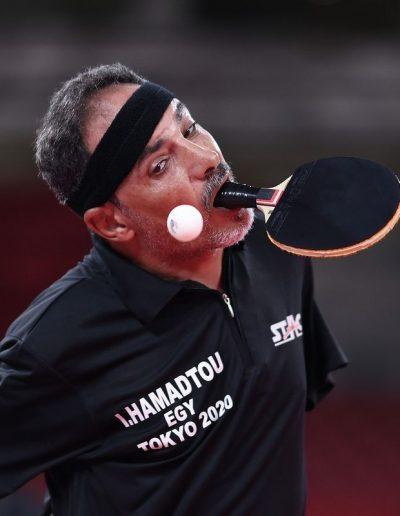 """Fotografía de Ibrahim Hamadtou del equipo egipcio haciendo un rallye de tenis de mesa, él es un hombre de edad adulta con cabello de color negro con algunas canas, utiliza una banda de tela alrededor de su cabeza para detener el sudor que cae sobre su frente, mira hacia la pelota frente a él suspendida en el aire y sostiene con su boca una paleta de tenis de madera de color negro, el paratleta viste una playera de color negra que en la parte izquierda tiene escrito: """"Hamadtou, Tokio 2020""""."""