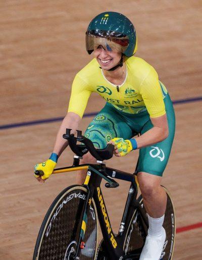 Fotografía de la paratleta Paige Greco del equipo Australia, viste un traje completo con playera de manga larga y bermuda, de color verde con amarillo, utiliza casco verde con amarillo y se encuentra sentada sobre una bicicleta color negra; ella sonríe después de ganar el oro en ciclismo femenino, la primera medalla de oro de los Juegos Paralímpicos de Tokio 2020.